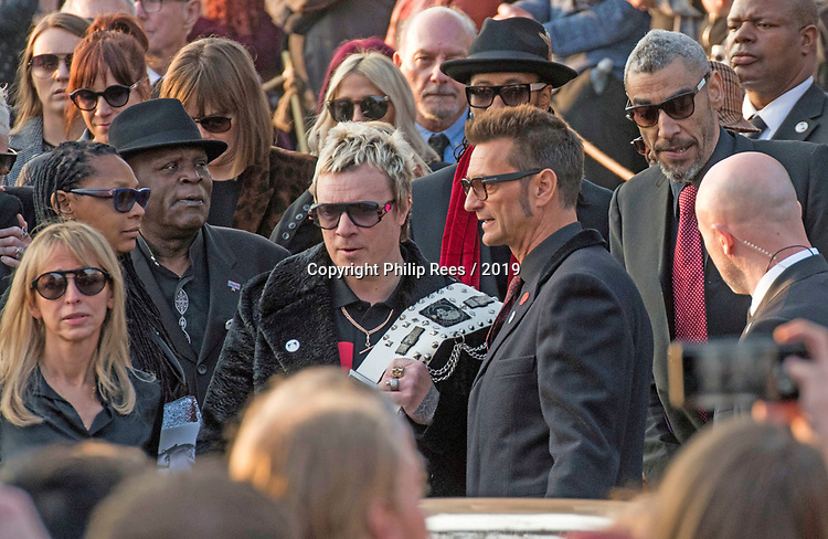 The  funeral of Prodigy singer Keith Flint at St Marys Church in Bocking,  Essex today. Laim Howlett of the Prodigy leaves the service while carrying Keith's belt as Leeroy Thornhill follows to his right.