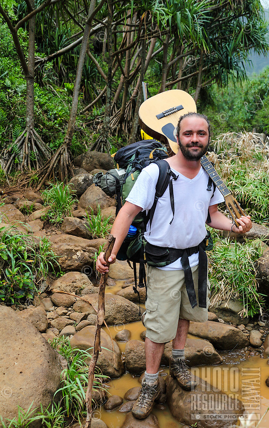 A backpacker with his guitar near Hanakapi'ai Steam along the Kalalau Trail on Kaua'i.