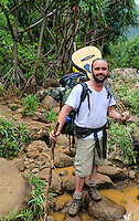 A backpacker with his guitar near Hanakapi'ai Steam along the Kalalau Trail on Kaua'i.