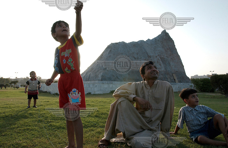 The Polo Park, central Karachi. A family fly a kite in front of a replica of the Chagai mountain inside which Pakistan conducted its first nuclear test. The country is very proud of its status as the only Muslim nuclear power.