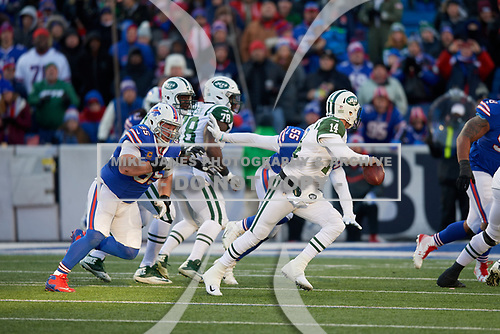 New York Jets quarterback Sam Darnold (14) scrambles under pressure from Kyle Williams (95) during an NFL football game against the Buffalo Bills, Sunday, December 9, 2018, in Orchard Park, N.Y.  (Mike Janes Photography)