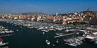 Aerial, panoramic view of basilica of Notre Dame de la Garde and the old port, in Marseille under a blue sky, at the border of the French Riviera