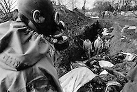 Russian soldiers wearing gas masks examine a mass grave to look for their fallen comrades. Countless unidentified bodies, the majority civilians, were dumped here after the battle for Grozny...
