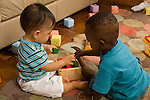 15 month old and 12 month old toddler baby boys both plyaing with shape sorter toy together horizontal