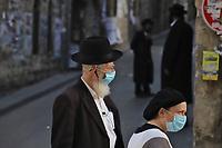 Una pareja vistiendo barbijos camina por el barrio ultraortodoxo Mea Shearim. En un esfuerzo por detener el contagio del COVID 19 el gobierno israelí decreto el uso obligatorio de barbijos en las calles. La pandemia ha afectado fuertemente a la comunidad Haredi.<br /> Foto Quique Kierszenbaum