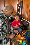 Father in kitchen with 3 year old son, boy talking about activity, cutting sweet peppers