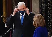United States Vice President Mike Pence adjusts his face mask as he and Speaker of the United States House of Representatives Nancy Pelosi (Democrat of California), preside over the Electoral College vote certification for President-elect Joe Biden, during a joint session of Congress at the U.S. Capitol in Washington, DC on Wednesday, January 6, 2021.<br /> CAP/MPI/RS<br /> ©RS/MPI/Capital Pictures