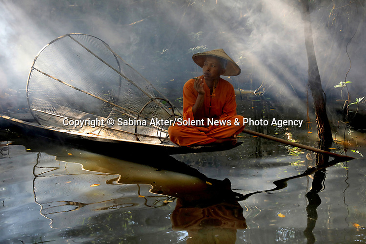 Pictured:   A fisherman skillfully balances on his boat as he makes his way through a mangrove forest.<br /> <br /> He balances on one leg whilst using the other to row using a wooden oar.<br /> <br /> The fisherman carried a conical fishing net whilst looking through the reeds for fish to catch. SEE OUR COPY FOR FULL DETAILS.<br />  <br /> Please byline: Sabina Akter/Solent News<br /> <br /> © Sabina Akter/Solent News & Photo Agency<br /> UK +44 (0) 2380 458800