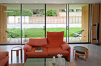 The contemporary living area features floor to ceiling windows and sofas by Vico Magistretti