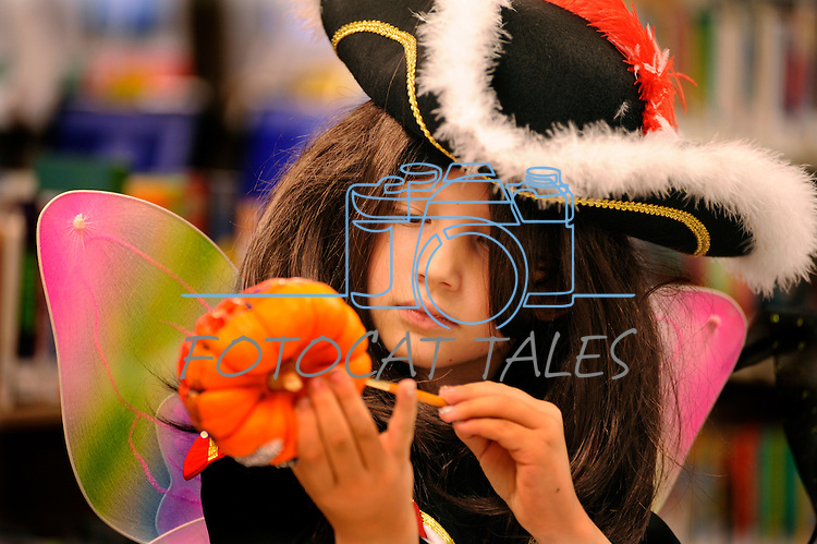 Freya Resler, 6, creates some art at the Carson City Library Monday, Oct. 27, 2014. As part of the library's Halloween festivities, dozens of children decorated pumpkins and took part in a costume contest.