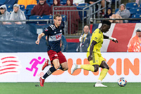 FOXBOROUGH, MA - AUGUST 4: Jalil Anibaba #3 of Nashville SC dribbles as Adam Buksa #9 of New England Revolution closes during a game between Nashville SC and New England Revolution at Gillette Stadium on August 4, 2021 in Foxborough, Massachusetts.