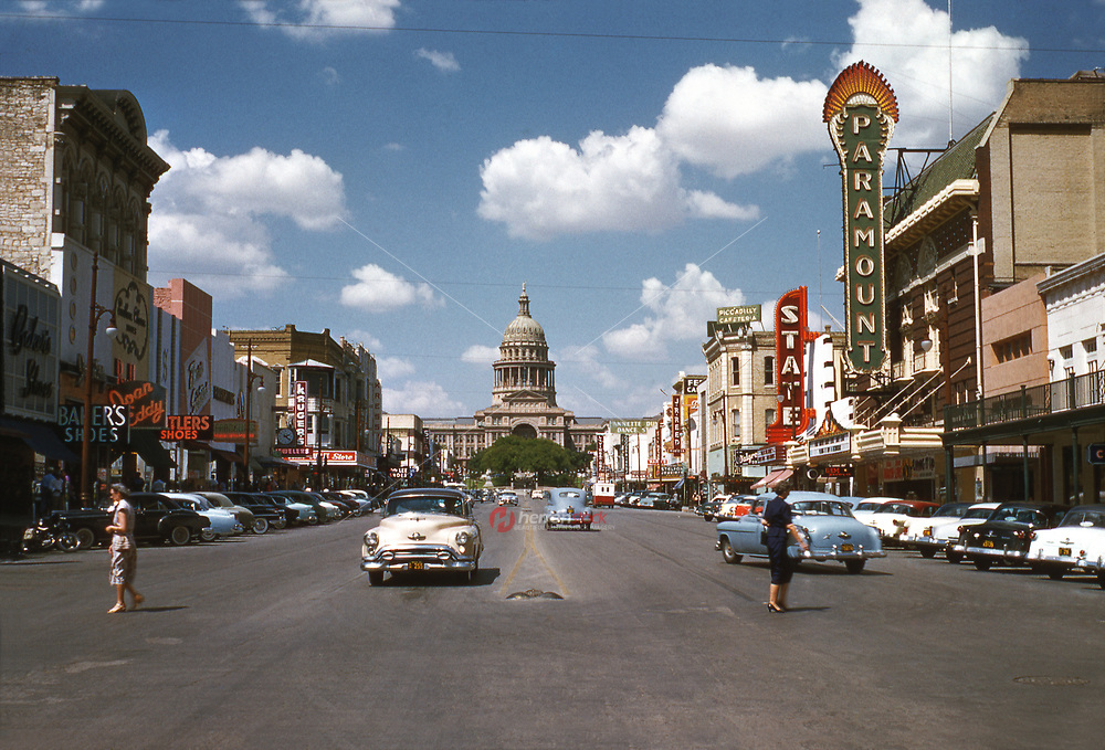 Historical view in 1954 of Congress Avenue with two ladies crossing the street in period dress and vintage Cadillac cars driving past the Paramount and State Theatre up to the Texas State Capitol in downtown Austin, Texas.