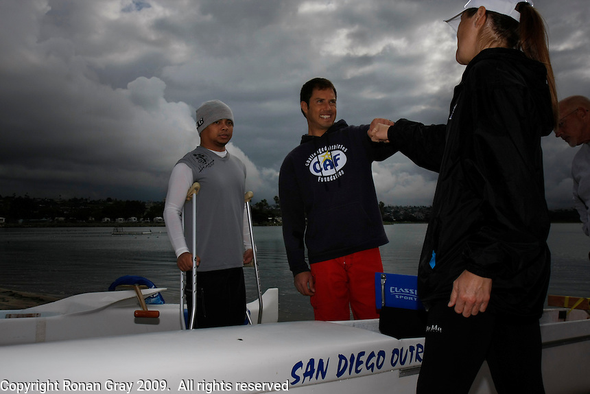 Saturday, 01/24/09.  Campland on the Bay, Mission Bay, San Diego, CA, USA.  Ryan Levison (c) greets outrigger paddling outrigger canoe instructor Nicole Holbrook as Carlito Butalip (L) looks on during an event sponsorded by the Challenged Athletes Foundation that Levinson was primarily responsible for organizing.  The participants had the opportunity to try several different paddle sports.  The Challenged Athletes Foundation established the Operation Rebound fund to provide sports opportunities and support for troops, veterans and first responders who have suffered permanent physical injuries in the line of duty.  Butalip is missing his right leg and Levinson - an accomplished triatholon, cyclist and waterman - has FSH Muscular Dystrophy (FSHMD), an incurable, untreatable, muscle-wasting disorder.