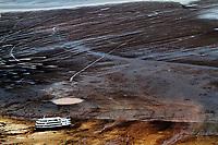 """Iranduba  Amazonas 25 10 2010 RECORDE VAZANTE- SECA AMAZONAS. Barco  no meio do leito rio seco em frente a cidade de Manaus, o rio Negro sofreu a maior vazante da história. A série """"Uma certa Amazônia"""" realizada durante a primeira década do século  21, quando os eventos extremos de cheia e vazante na Amazônia revelaram que algo de muito errado está acontecendo com o clima do planeta. Mudanças cada vez mais drásticas no regime das águas da bacia dos rios Negro e Solimões provocaram impactos como a fome, sede, doenças e mortandade de animais. O cotidiano das populações tradicionais e a paisagem amazônica mudaram definitivamente. Uma situação de extremos, onde as vazantes estão, a cada ano, se transformando em catástrofes e as cheias mostrando-se cada vez mais trágicas. Este cenário que a cada vez mais perde áreas de florestas para o agronégocio, principalmente  as plantações de soja e milho, assim como a criação de gado, além da pressão sofrida pela industria madereira em áreas de preservação permanente e também em terras indígenas, além  da exploração mineral e a ameaça pelas grandes obras de infra-estrutura do governo brasileiro fazem da Amazônia um dos ecossistemas mais frágeis perante a ação do homem."""
