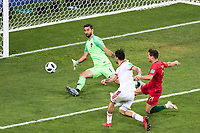 SARANSK, RUSSIA - June 25, 2018: Mehdi Taremi of Iran attempts to shoot a goal past  Goalkeeper Rui Patricio of Portugal while Portugal defender Cedric Soares looks on in their 2018 FIFA World Cup group stage match at Mordovia Arena. He missed just wide.