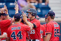 Matt Snyder #33 of the Ole Miss Rebels is congratulated by his teammates after scoring a run against the St. John's Red Storm at the Charlottesville Regional of the 2010 College World Series at Davenport Field on June 6, 2010, in Charlottesville, Virginia.  The Red Storm defeated the Rebels 20-16.  Photo by Brian Westerholt / Four Seam Images
