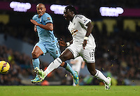 Picture by Howard Roe/AHPIX.com. Football, Barclays Premier League; <br /> Manchester City v Swansea City ;22/11/2014 KO 3.00 pm <br /> Etihad Stadium;<br /> copyright picture;Howard Roe;07973 739229<br /> Swansea's     Bafetimbi Gomis puts the ball past Manchester's keeper Joe Hart but also wide of the post