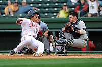 Catcher Jayson Hernandez (12) of the Greenville Drive slams into catcher Peter O'Brien (9) of the Charleston River Dogs while trying to score what would have been the winning run on a hit in the bottom of the seventh inning of a game on Saturday, April 6, 2013, at Fluor Field at the West End in Greenville, South Carolina. Charleston went on to win Game 1 of a doubleheader, 6-2. (Tom Priddy/Four Seam Images)