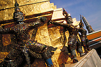 Ornately detailed statues holding up gold plated wall at the Grand Palace. Bangkok, Thailand.