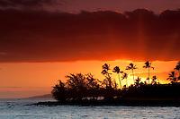 Sunset and palm trees off Poipu coast. Kauai, Hawaii