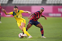 KASHIMA, JAPAN - AUGUST 5: Caitlin Foord #9 of Australia is marked by Crystal Dunn #2 of the United States during a game between Australia and USWNT at Kashima Soccer Stadium on August 5, 2021 in Kashima, Japan.