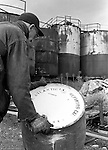 Lawrenceville PA: Location photography at the Atlantic Refining site at 5733 Butler Street. View of a workman moving a barrel full of oil.<br /> This track of land has been involved in oil-related refining for over 100 years.  ARCO sold the property to SUNOCO which still operates a storage facility at 5733 Butler Street.