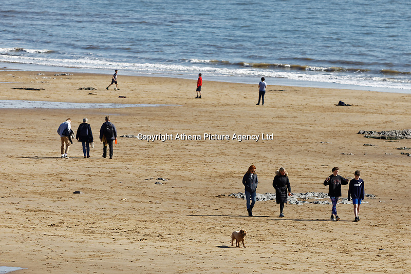 Pictured: People enjoy the sunshine by walking on the beach at Langland Bay near Swansea, Wales, UK. Sunday 22 March 2020<br /> Re: Covid-19 Coronavirus pandemic, UK.