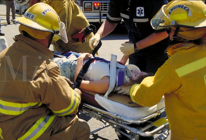 Fire safety personnel stabilizing accident victim at the scene. Paramedics. Emergency medical treatment. California.