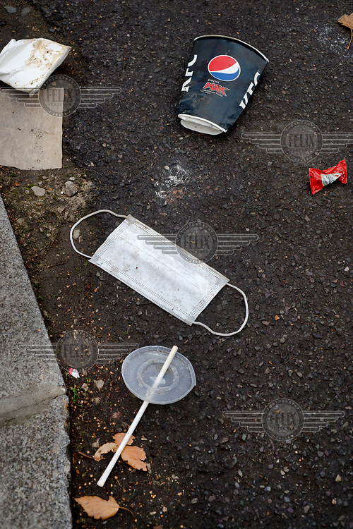A discarded face mask lies on Triangle Road among waste from a KFC fast food outlet, LB Hackney.
