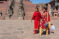 Bhaktapur, Nepal.  Women Walking through Taumadhi Tole Square.  Rajput Wrestler-guardians Jayamel and Phattu  Guard Stairs leading to Nyatapola Temple in Background.