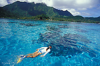 Woman snorkeling on reef in clear water in Raiatea, Tahiti, French Polynesia