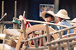 Two boys wearing pith hats wait in an oxcart at the Pyay marketplace, Burma.