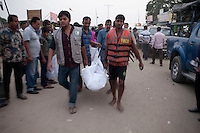 Bangladeshi rescue workers carry the dead body of one of the victims after a river ferry carrying more than 100 passengers capsized in the River Padma Sunday after being hit by a cargo vessel at Paturia , in Manikganj district, about 80 kilometers  northwest of Dhaka, Bangladesh. Feb. 22, 2015
