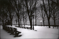 Snow covered benches with solitary light<br />