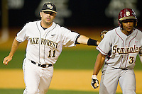 Wake Forest Demon Deacons shortstop Pat Blair #11 tags out Sherman Johnson #32 of the Florida State Seminoles after getting him caught in a run-down between first and second base at Wake Forest Baseball Park on March 24, 2012 in Winston-Salem, North Carolina.  The Seminoles defeated the Demon Deacons 3-2.  (Brian Westerholt/Four Seam Images)