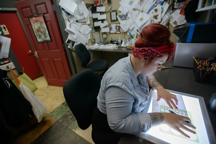 Brie Felts designs a tattoo for Valerie Gunther's leg at Primal Instinct Tattoo. Photo by James R. Evans
