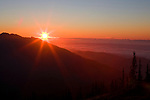 The sun flares as it sits on the lip of a fog bank setting over the Olympic Mountains and the Strait of Juan de Fuca as viewed from Deer Park in Olympic National Park. Olympic Peninsula