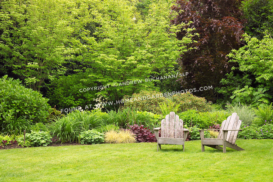 Two Adirondack chairs offer a quite, peaceful place to sit in the garden.