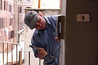 Operai edili mettono la porta blindata ad un appartamento..Construction workers put the armored door an apartment....