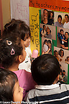 Preschool 2-3 year olds group of children gathered around display of photos showing the parents with their children separation vertical