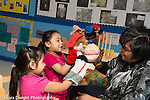 Education Preschool  4 year olds female teacher and two girls playing with human and animal puppets