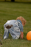 A SMALL TODDLER BENDING OVER REVEALING THE DIRT ON HIS PANTS