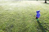 Little girl running through dew coverred grass