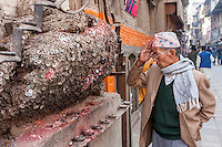 Nepal, Kathmandu.  Man Praying for no Toothache at the Shrine to the Toothache God, Bangemudha Square.