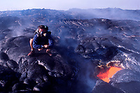 hiker wearing respirator to protect himself from the deadly hydrochloric gases emitting from this skylight of lava, Hawaii Volcanoes National Park, Big Island of Hawaii, USA