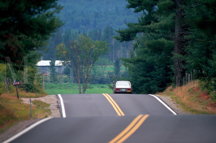 Car driving down a winding, rolling country road. New Hampshire.
