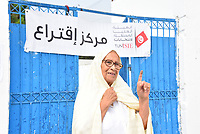 TUNIS, TUNISIA - SEPTEMBER 15: Tunisian woman shows her inked finger after casting her vote at a polling station during the presidential elections in Tunis, Tunisia on September 15, 2019.