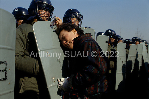 """Kuro gu, South Korea.December 18, 1987..A mother is separated from her arrested son by a wall of government police after a battle with students at a nearby polling station. The students claim that the polling station had been the filled with fraudulent votes....After two decades of building an economic miracle, in the summer of 1987 tens of thousands of frustrated South Korean students took to the streets demanding democratic reform. """"People Power"""" Korean-style saw Koreans from all social spectrums join in the protests...With the Olympics to be held in South Korea in 1988, President Chun Doo Hwan decided on no political reforms and to choose the ruling party chairman, Roh Tae Woo, as his heir. The protests multiplied and after 3 weeks Chun conceded releasing oppositionist Kim Dae Jung from his 55th house arrest and shaking hands with opposition leader Kim Young Sam. Days later he endorsed presidential elections and an amnesty for nearly 3,000 political prisoners. It marked the first genuine initiative of democratic reform in South Korea and the people had their victory."""