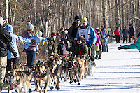 Travis Beals and team run past spectators on the bike/ski trail during the Anchorage ceremonial start during the 2014 Iditarod race.<br /> Photo by Britt Coon/IditarodPhotos.com