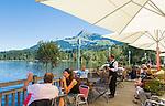 Austria, Tyrol, near Kitzbuhel: Café and restaurant at idyllic Schwarzsee (Black Lake) on the outskirts of Kitzbuhel, at background mountain Kitzbuheler Horn | Oesterreich, Tirol, bei Kitzbuehel: Café und Restaurant am Schwarzsee, idyllisch gelegener Badesee, 8 ha gross und bis zu 8 m tief, einer der waermsten Seen der Alpen, im Hintergrund das Kitzbueheler Horn